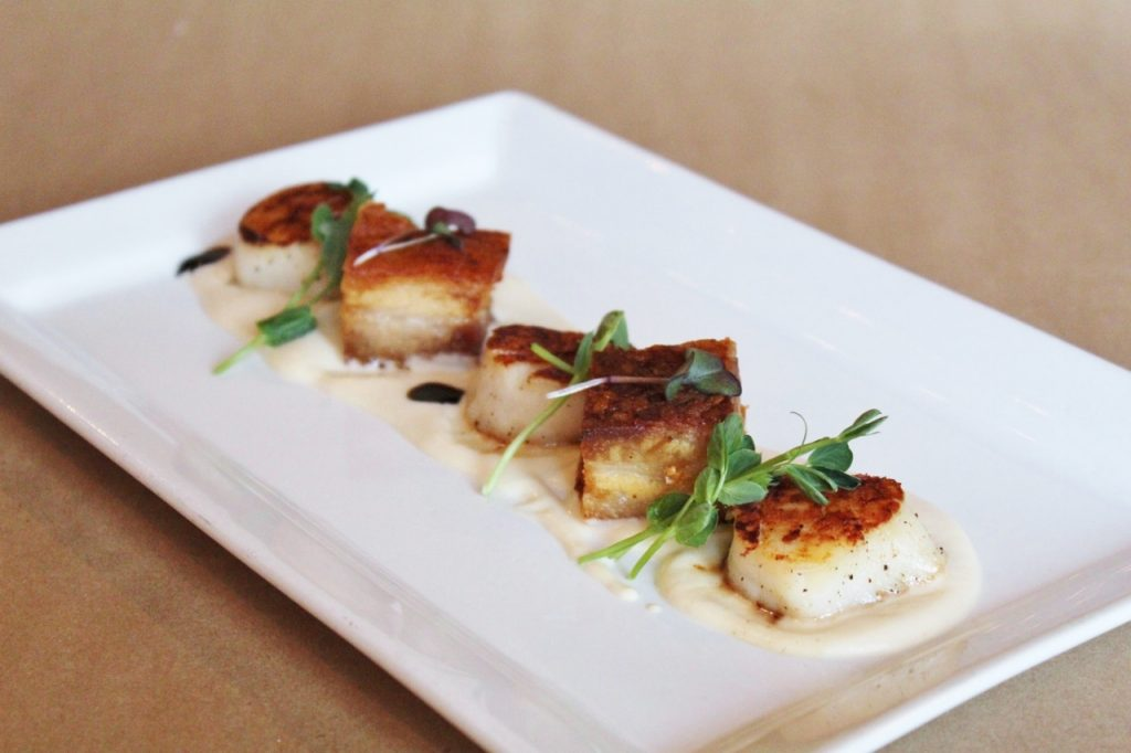Five scallops plated as an appetizer with microgreens and a white puree