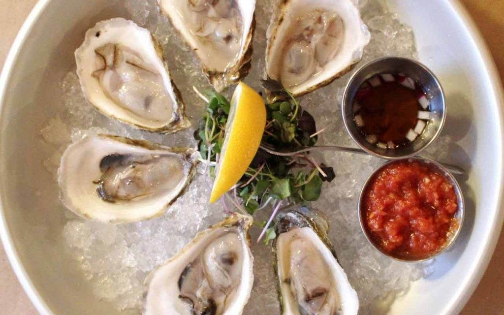 Half dozen oysters on ice with mignonette sauce, cocktail sauce, and lemon