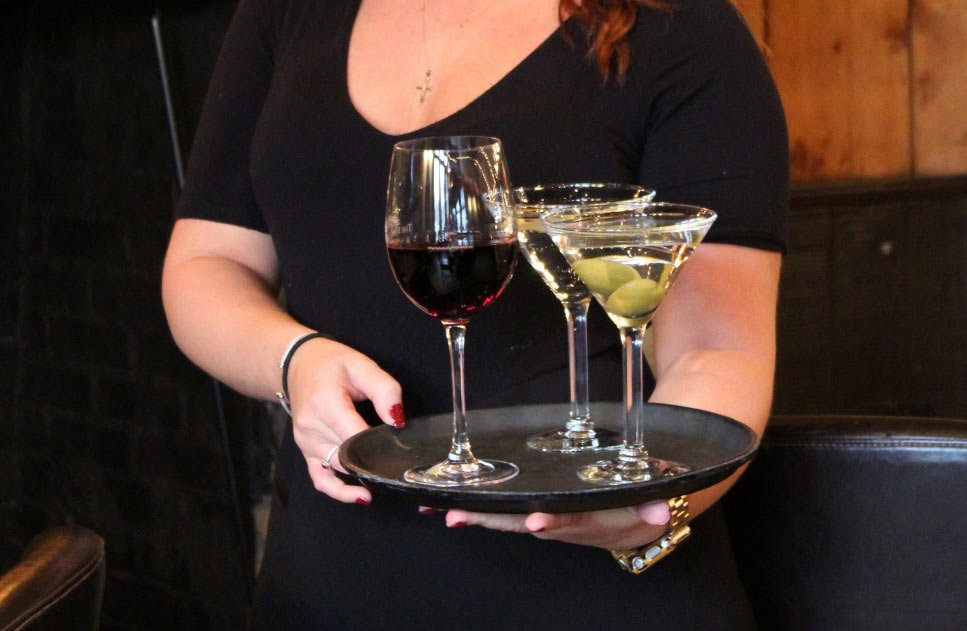 A glass of red wine and two martinis being carried by a waitress in black