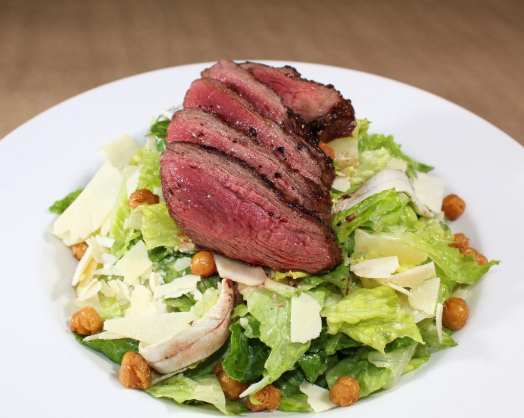 a medium rare steak atop a Caesar salad