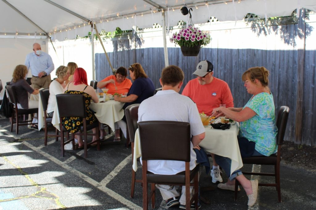 People eating outdoors under a tent