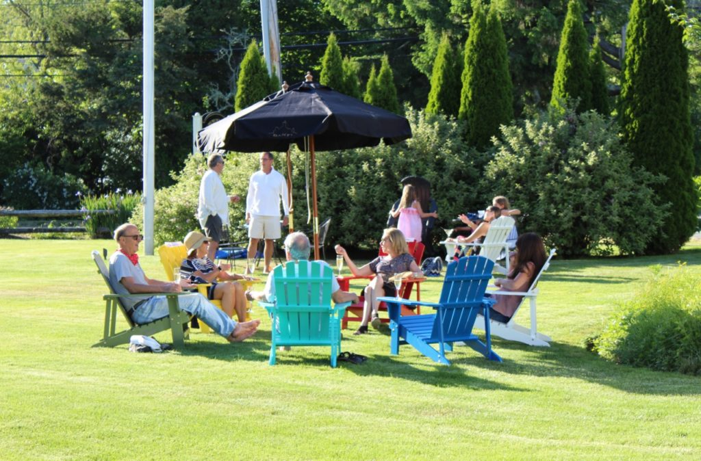 People sitting in adirondack chairs on the lawn with drinks