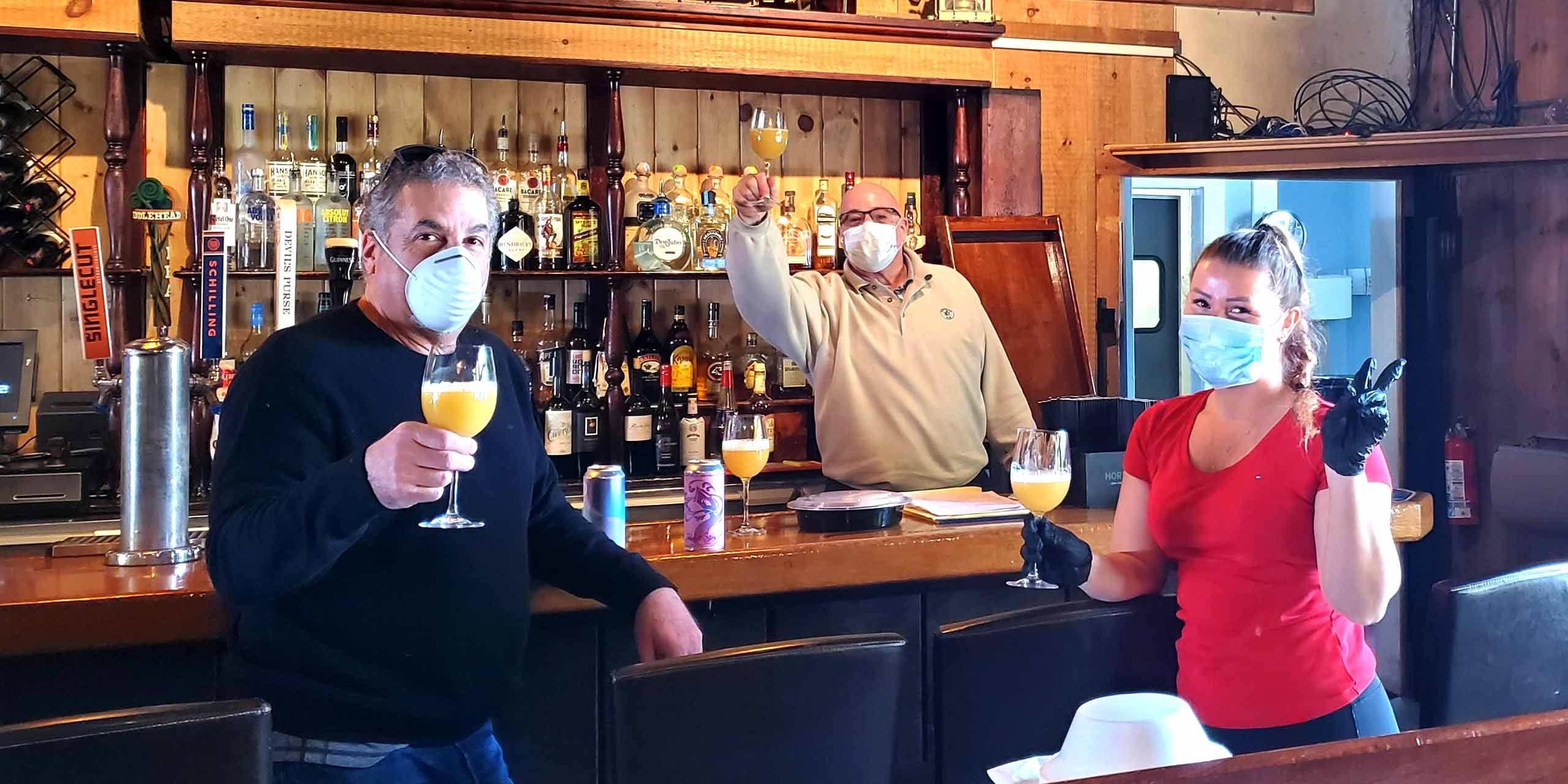 The owners and a server raise glasses of beer at the bar while wearing masks
