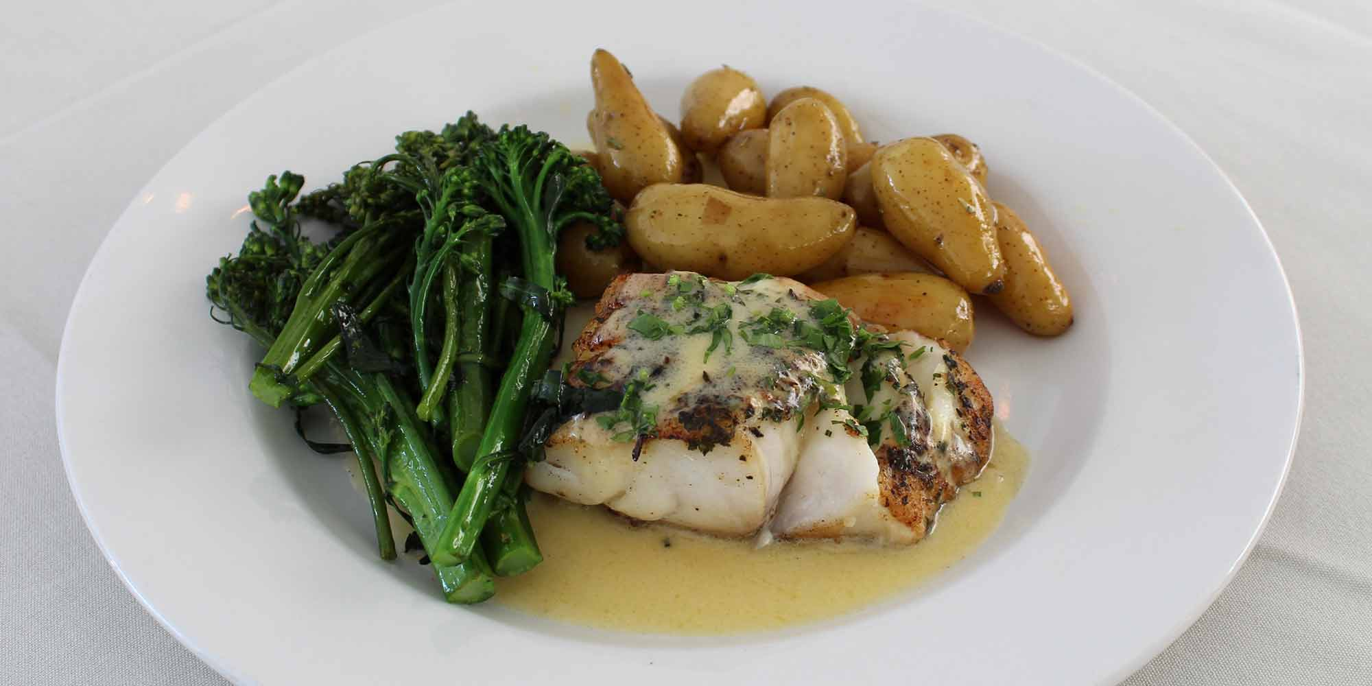 pan fried cod with butter sauce. brocollini and potatoes