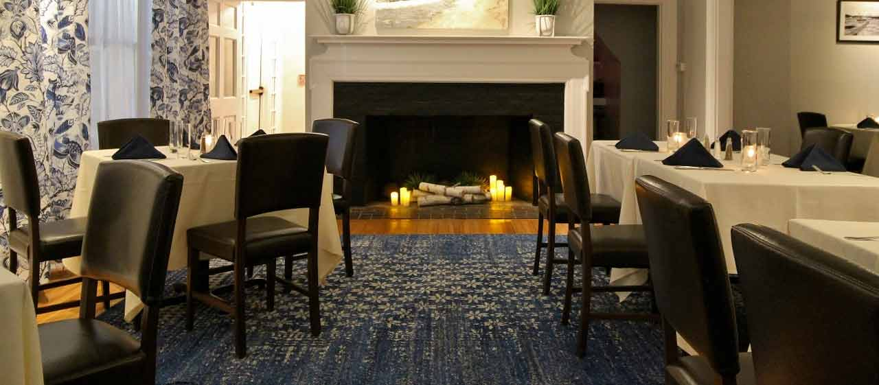 Blue rug and fireplace in a function room with white linens
