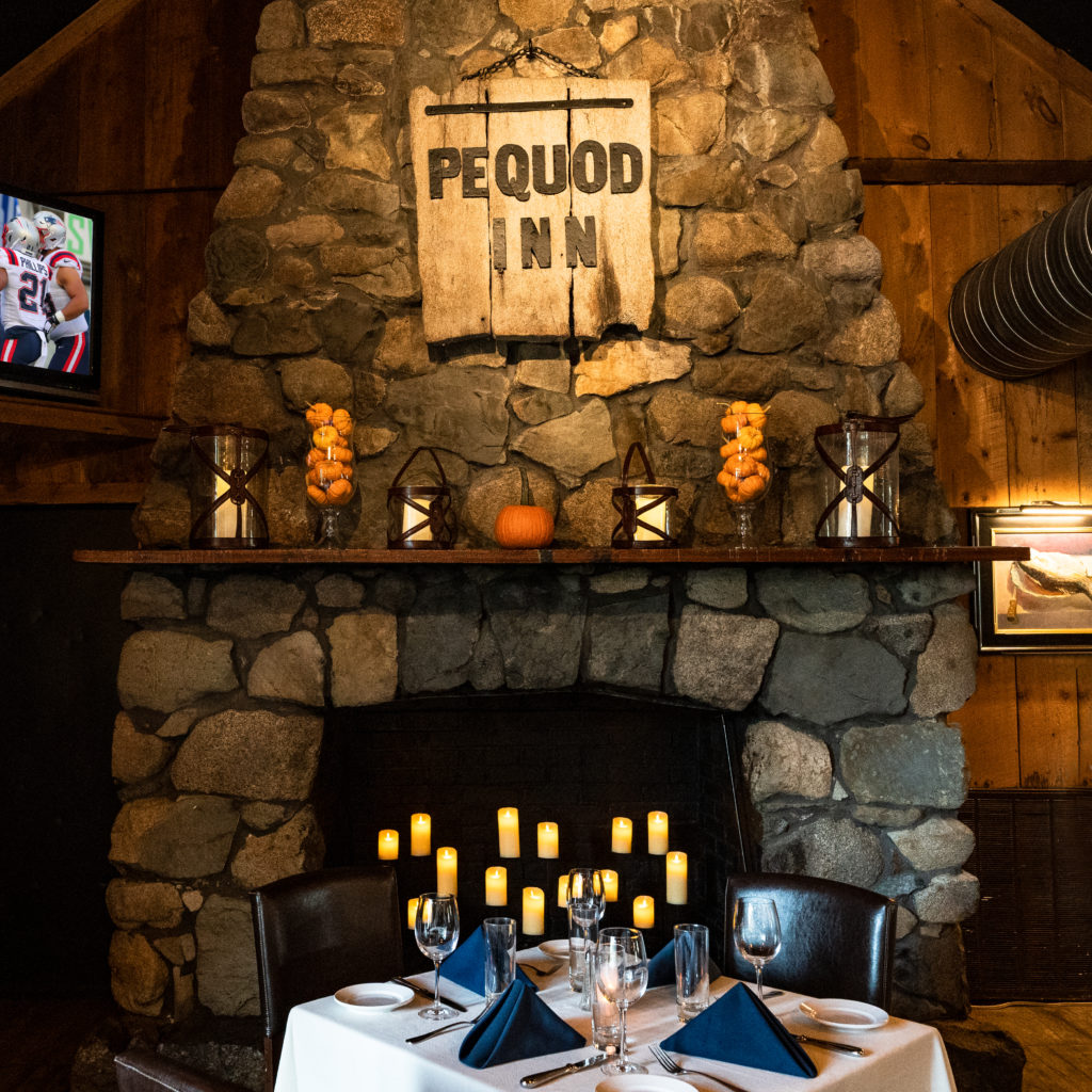 Pequoid Inn sign above fireplace with fall decor